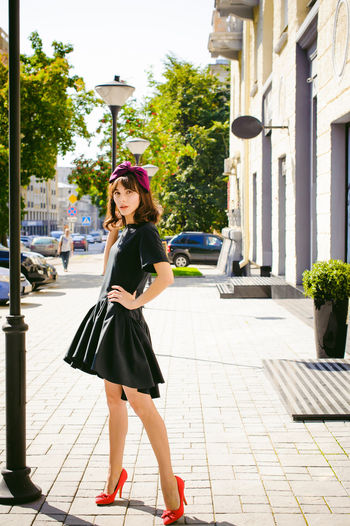 Beautiful young woman in black dress standing on sidewalk in city