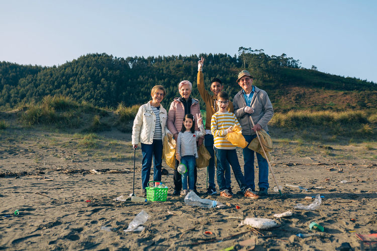 Portrait of happy family cleaning beach