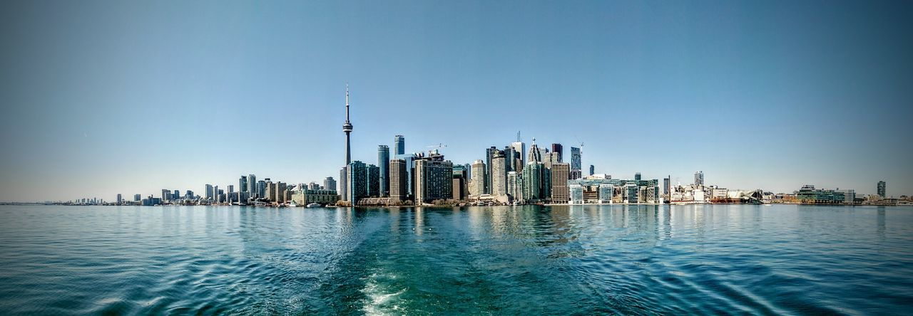 Panoramic shot of sea by cn tower and city against clear blue sky