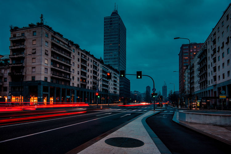 Light trails on city street by buildings against sky at dusk milan italy