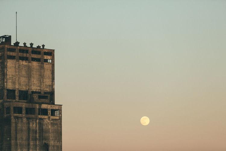Full moon beside old grain elevator.