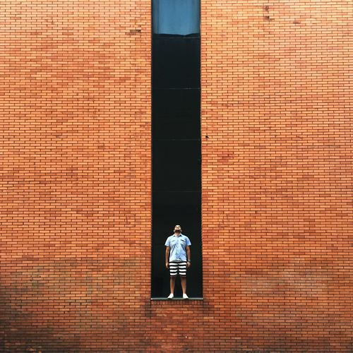 Man standing on retaining wall of red brick wall