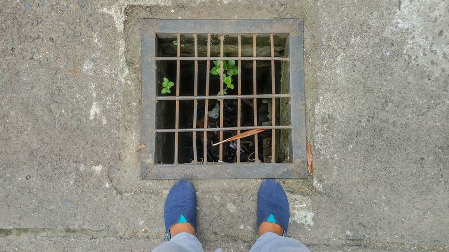 Low section of person standing on street by sewer