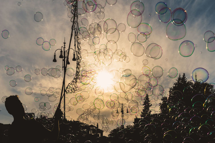 Sun Lens Flare Sky No People Nature Plant Tree Sunlight Beauty In Nature Bubble Low Angle View Silhouette Outdoors Growth Shape Day Geometric Shape Circle Design Cloud - Sky Bright Brightly Lit