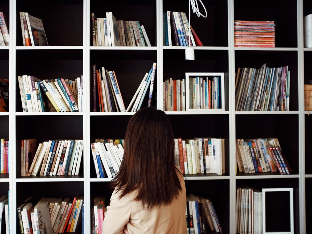 shelf, bookshelf, publication, rear view, book, education, women, large group of objects, one person, arrangement, library, leisure activity, indoors, adult, learning, real people, lifestyles, abundance, choice, hairstyle, literature, order, studying
