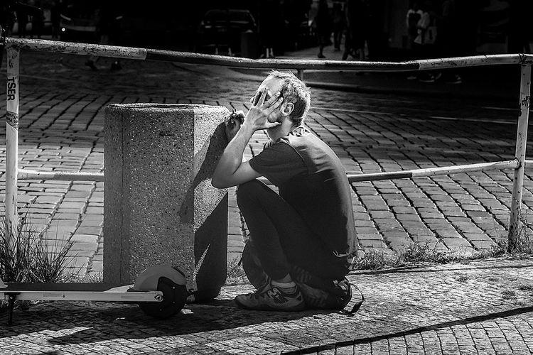 Portrait of man sitting on footpath