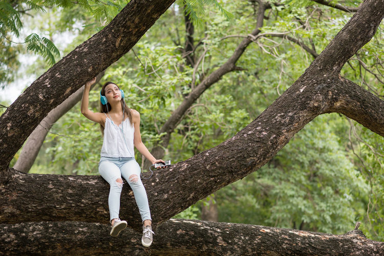Full length of woman leaning on tree trunk
