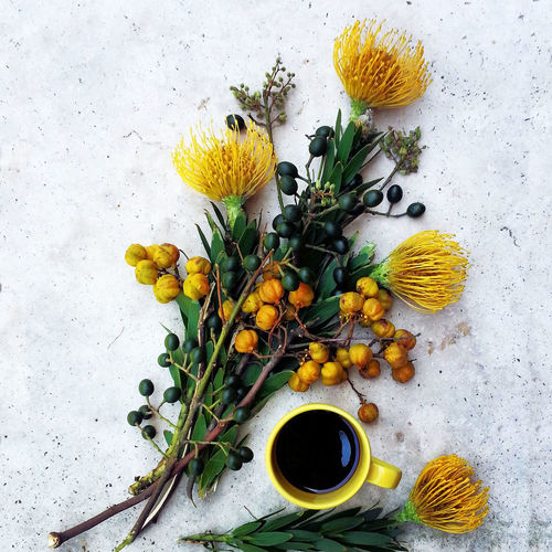 High angle view of yellow flowers and coffee on marble
