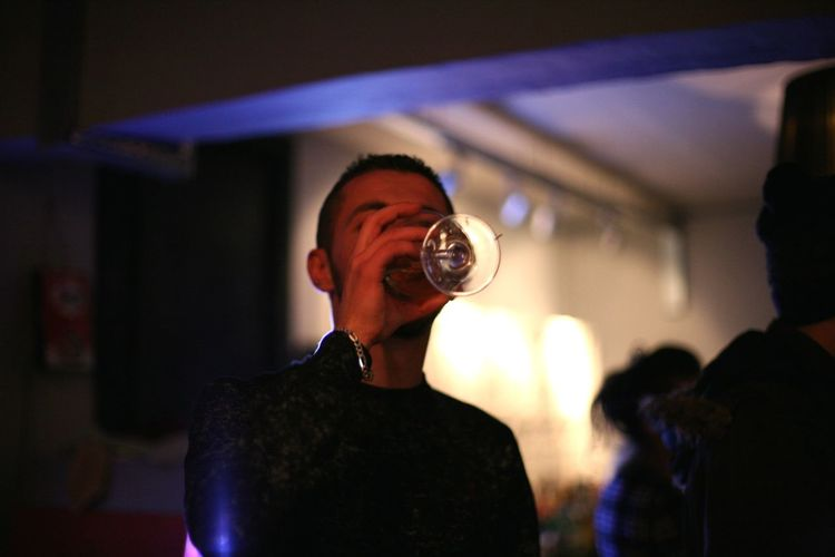 Young man drinking wine during party