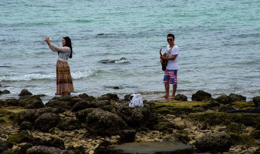 Woman standing on rocks by sea