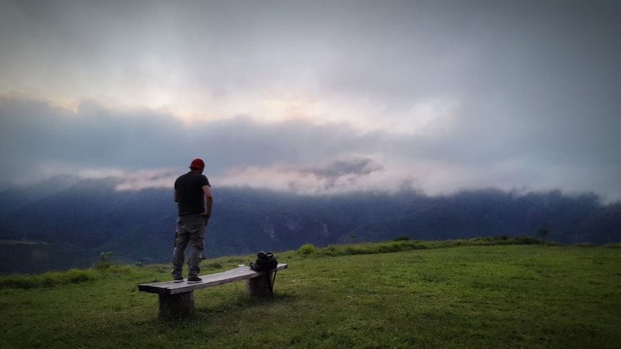 Rear view of man standing on bench against cloudy sky during sunset