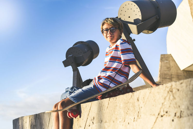 Portrait of boy sitting on wall against sky