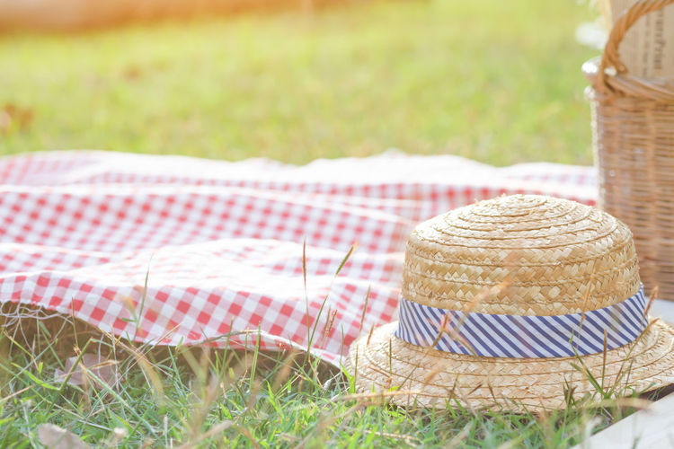 Close-Up Of Hat And Picnic Basket On Grassy Field