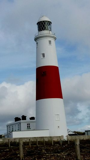 A Beautiful picture of a White and Red Painted Lighthouse Taken at Portsmouth . Featuring Guidance Protection Sky Cloud - Sky Direction Day Built Structure Building Exterior Architecture Beach Outdoors No People United Kingdom Travel Destinations History Light History