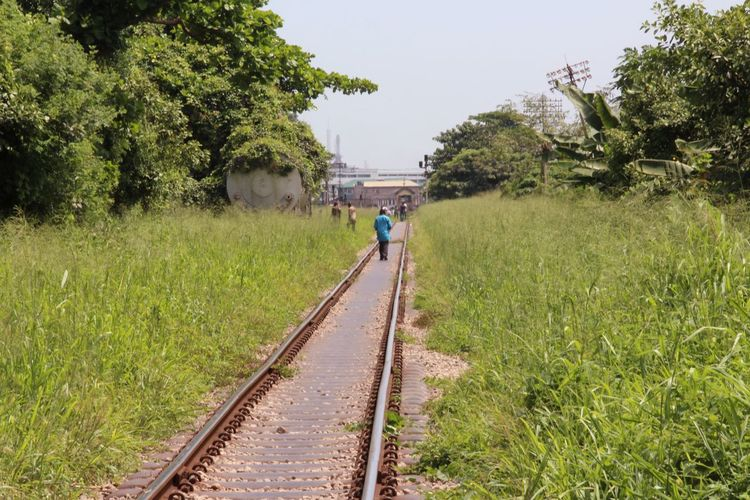 Full Length Rear View Of Man Walking On Railroad Track
