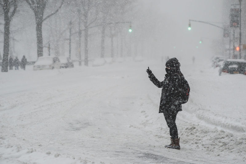 Person Taking Self Portrait While Standing On Street During Snowfall