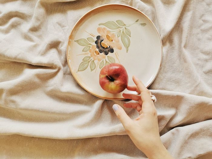 Cropped hand of woman holding apple in plate