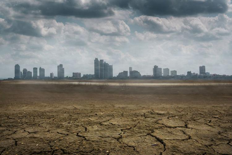 Cracked land against cityscape