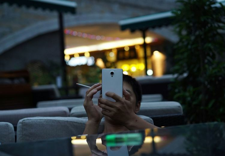 Man Holding Smart Phone And Cigarette In Outdoor Cafe
