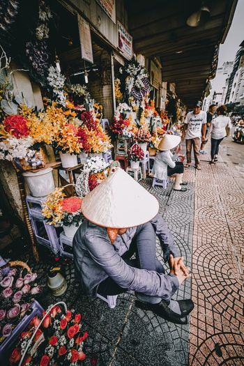 Vendor wearing asian style conical hat sitting at flower market in city