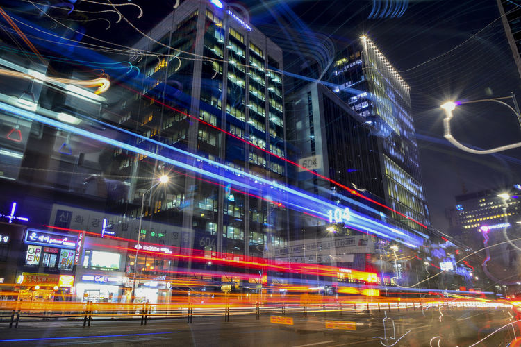 busy traffic at night Illuminated Night City Motion Architecture Building Exterior Long Exposure Built Structure Blurred Motion Street Light Trail Speed Road Transportation City Life Glowing Office Building Exterior Building No People Skyscraper City Street