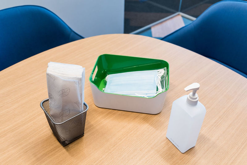 High angle view of hand sanitizer and surgical mask on table