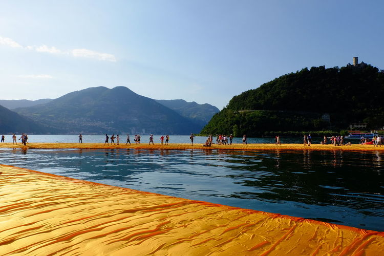 Beauty In Nature Blue Day Floating Piers Fujifilm Idyllic Lago D'Iseo Leisure Activity Lifestyles Medium Group Of People Mountain Mountain Range Nature Outdoors Remote Scenics Sky Tourism Tourist Tranquil Scene Tranquility Travel Destinations Unrecognizable Person Vacations Water