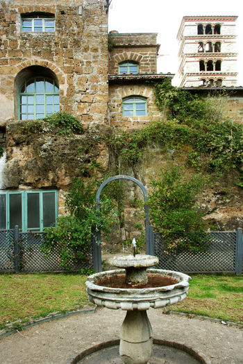 Fountain in the castle garden Brick Wall Castle Fountain Architecture Bell Tower Building Exterior Built Structure Climbing Plant Garden Grass Italy Lazio Medieval Medieval Architecture Medieval Castle Nature Outdoors Residential Building Via Amerina Water Window