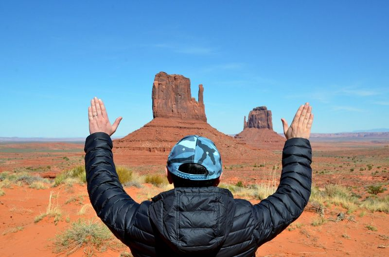 Rear view of man standing with arms raised at monument valley tribal park
