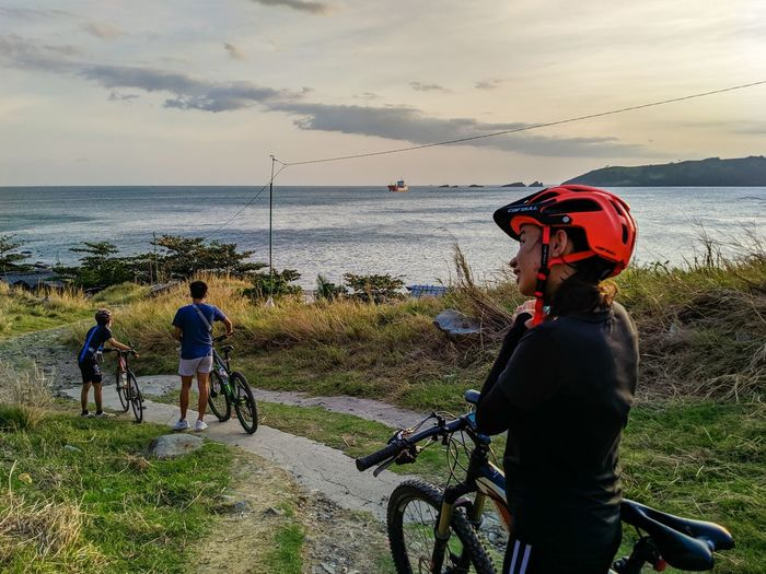 Rear view of men with bicycle by sea against sky