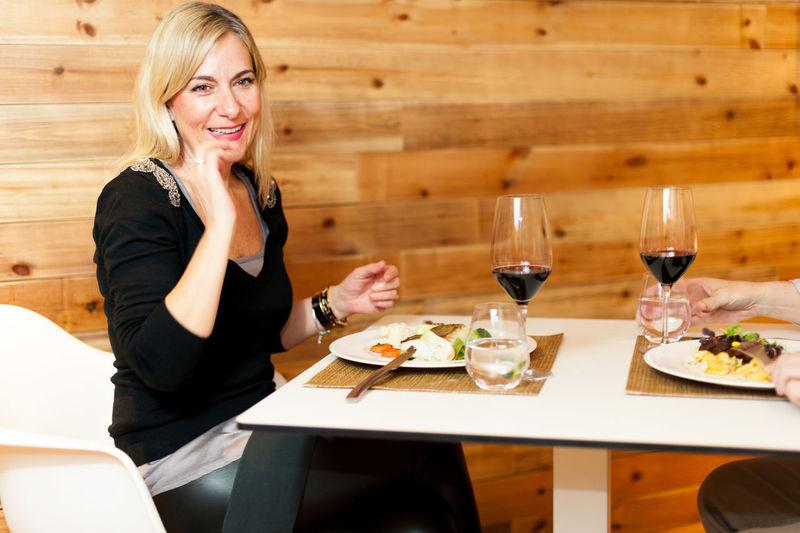 Portrait Of Smiling Woman Having Food At Restaurant
