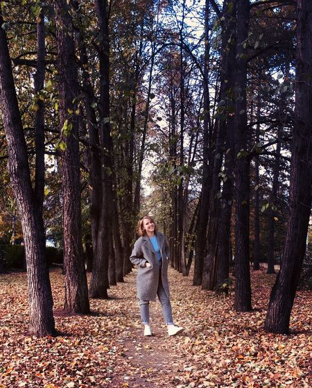 Full length of woman standing amidst trees in forest during autumn