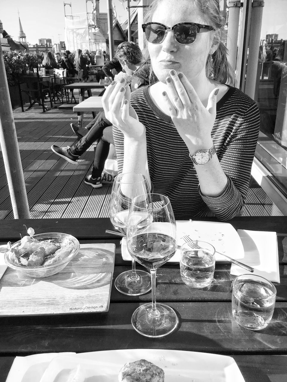 restaurant, food and drink, real people, drink, sunglasses, table, food, wine, drinking glass, one person, wineglass, sitting, alcohol, young adult, lifestyles, young women, outdoors, day, adult, people