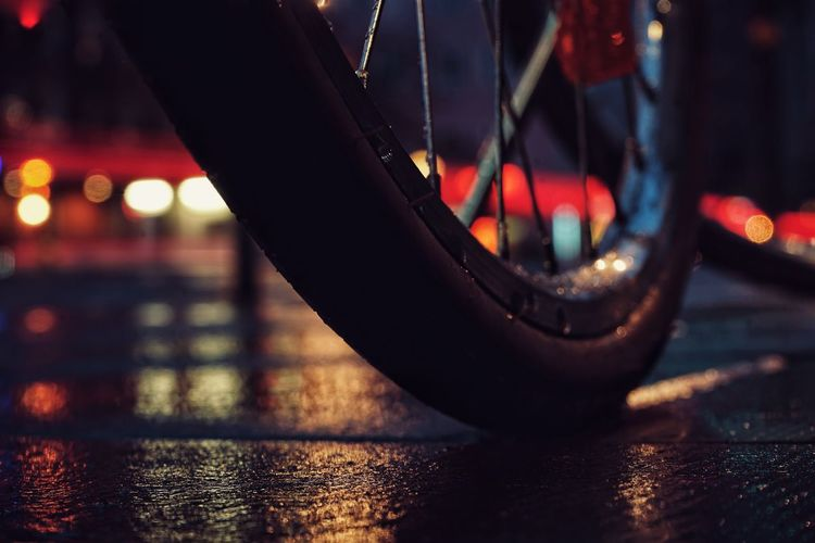 Close-up of bicycle parked on railing at night
