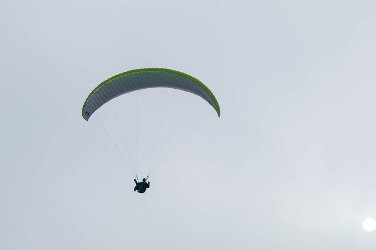 Low angle view of person paragliding against sky