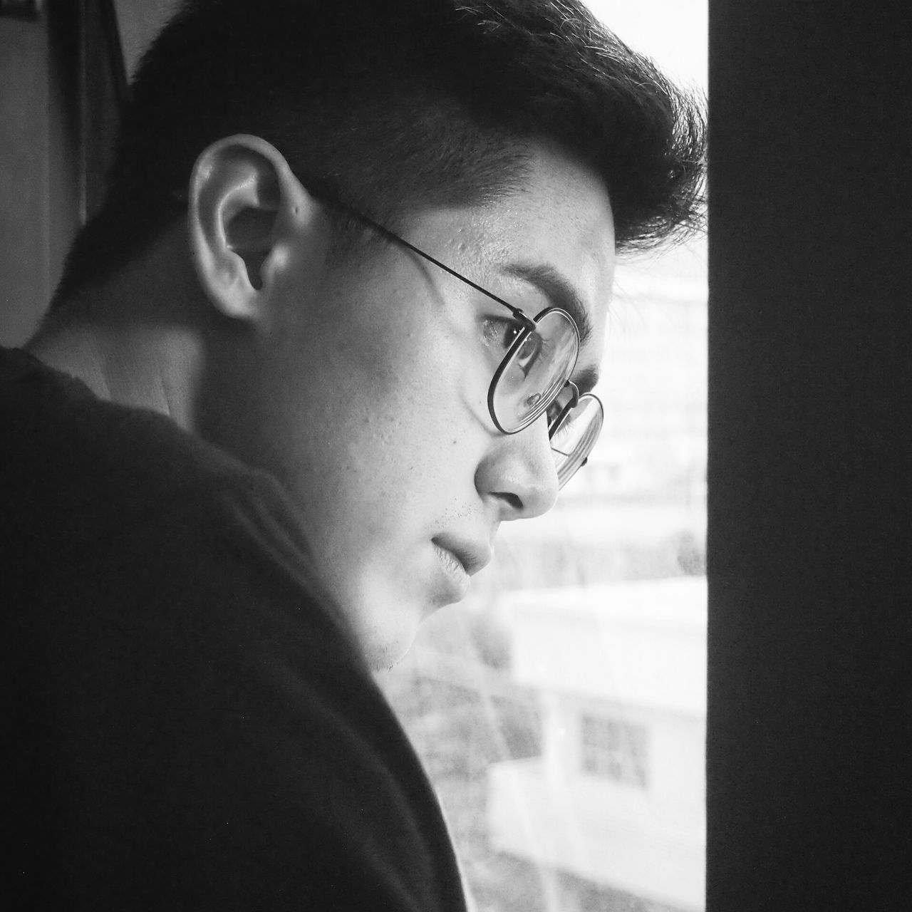 Close-Up Of Thoughtful Young Man Looking Through Window
