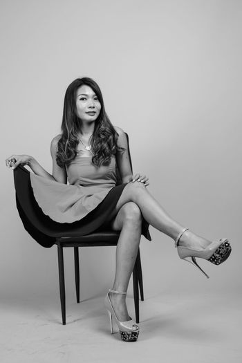 Portrait of woman sitting on chair against gray background