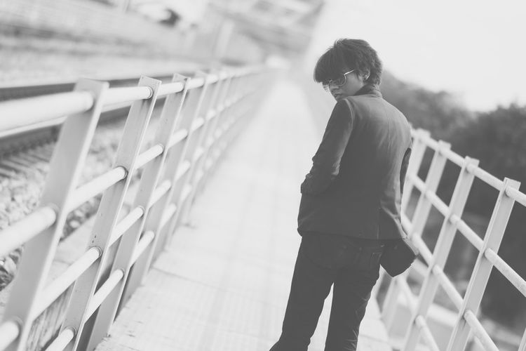 Rear view portrait of young man standing on footbridge
