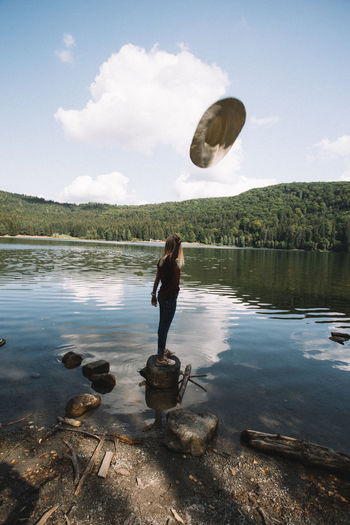 Full length of young woman throwing hat while standing by lake