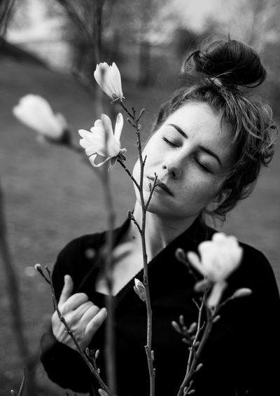 Woman with eyes closed standing by flowers