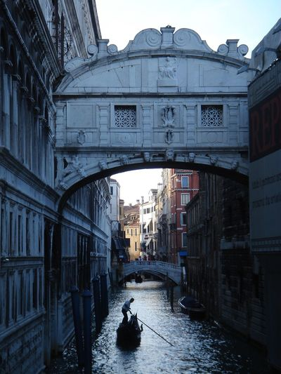 Man on gondola below bridge of sighs at grand canal in city