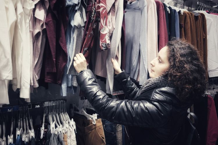 woman chooses clothes Choice Choosing Dress Fashion Hands Happy Lifestyle Shopping Woman Choices Choose Clothes Clothing Customer  Hand Jacket Retail  Shopper Store