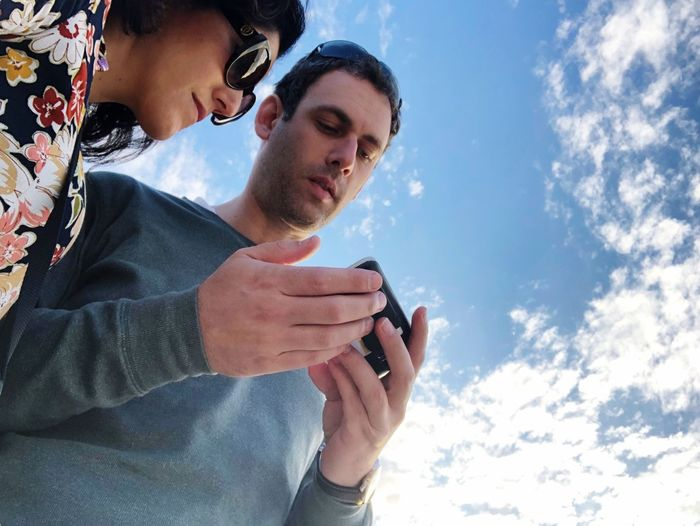 Low Angle View Of Couple Looking At Mobile Phone Against Sky