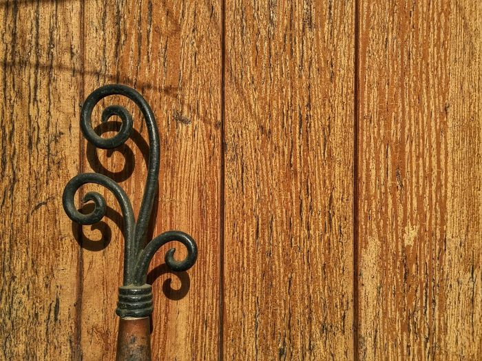 Close-up of wrought iron against wooden wall during sunny day