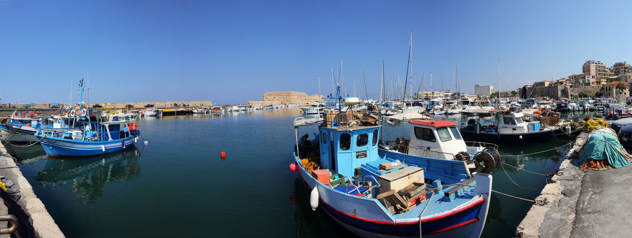 Blue Boat Building Exterior Built Structure City Clear Sky Crete Day Greece Harbor Heraklion Marina Mode Of Transport Moored Nautical Vessel Outdoors Port Sailboat Sea Sky Sunlight Transportation Travel Destinations Water Yacht