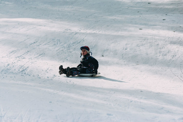 Cute boy sledding on snow covered field during winter