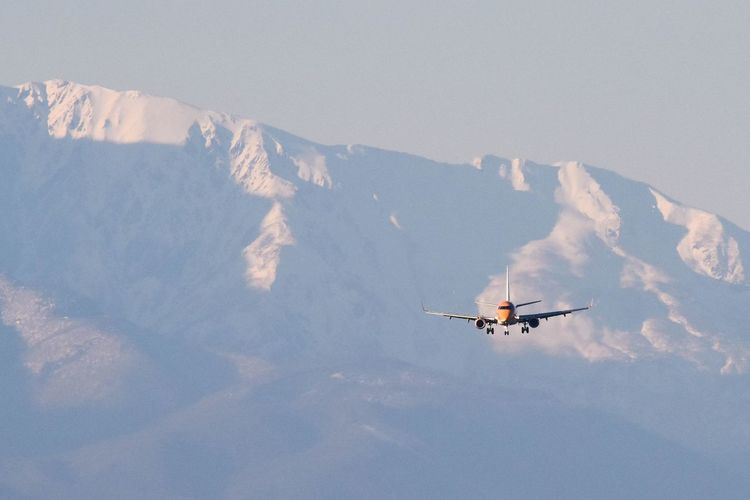 Low angle view of airplane flying against snowcapped mountains