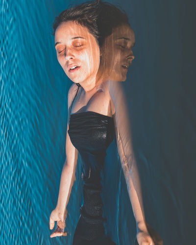 High Angle View Of Young Woman Swimming In Pool
