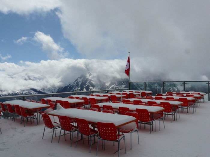 Empty chairs and tables against sky during winter