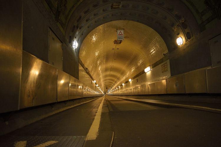 Illuminated empty tunnel at night